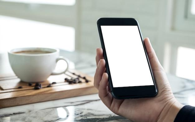 Mãos segurando um celular preto com tela branca em branco com uma xícara de café no café