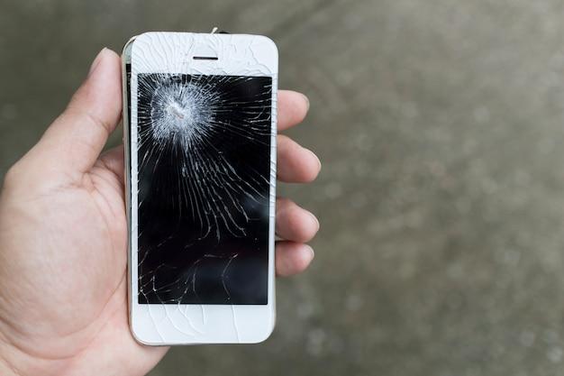 Mãos segurando um celular quebrado smartphone com tela quebrada.