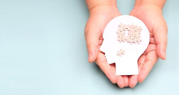 Mãos segurando um cérebro com recorte de papel de quebra-cabeça.