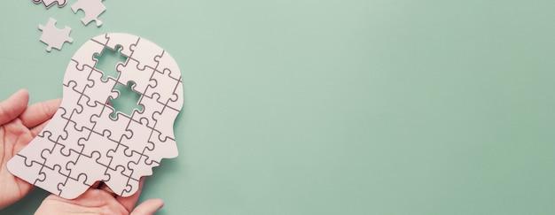 Mãos segurando um cérebro com recorte de papel quebra-cabeça, autismo, consciência de epilepsia e alzheimer, conceito do dia mundial da saúde mental