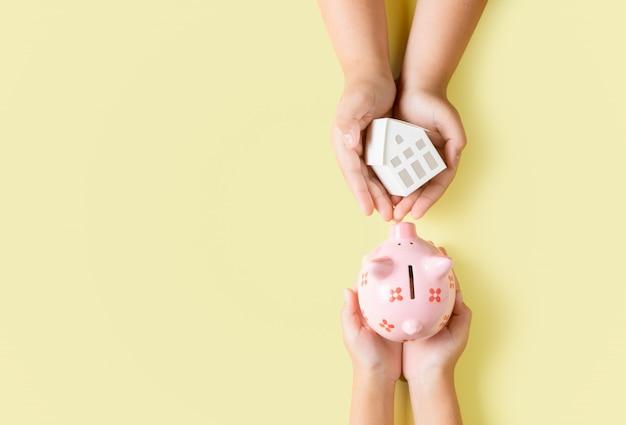 Mãos segurando um cofrinho rosa e casa modelo de papel