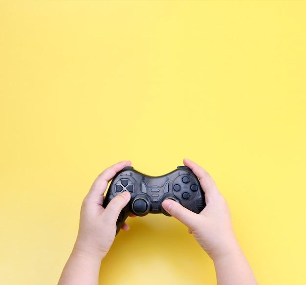 Mãos segurando um controlador de jogos joystick isolado em amarelo.