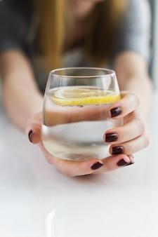 Mãos segurando um copo de água limpa com limão.