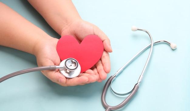 Mãos segurando um coração de papel vermelho com estetoscópio azul.