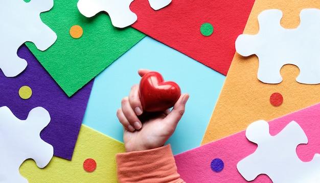 Mãos segurando um coração de pedra vermelha dia da conscientização mundial do autismo