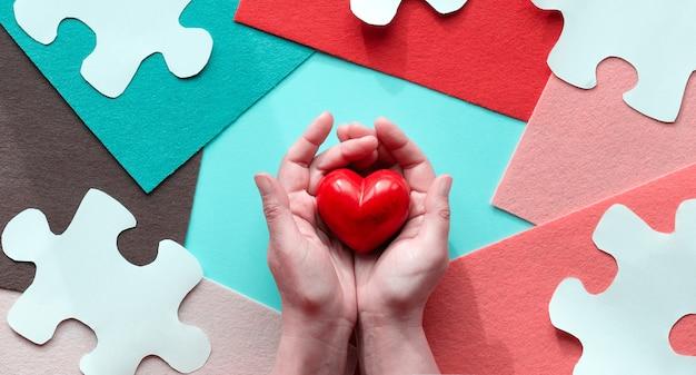 Mãos segurando um coração de pedra vermelha projeto criativo para o dia da conscientização mundial do autismo em abril