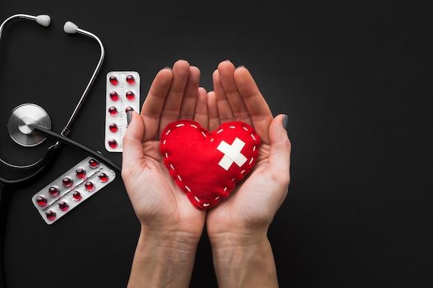 Mãos segurando um coração e comprimidos com estetoscópio no fundo