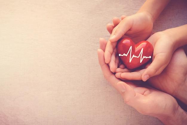 Mãos segurando um coração vermelho com eletrocardiograma, conceito de saúde do coração