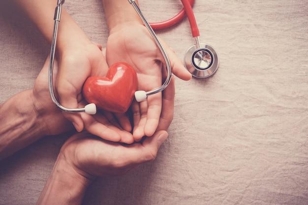 Mãos segurando um coração vermelho com estetoscópio, saúde do coração, conceito de seguro de saúde