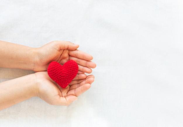 Mãos segurando um coração vermelho, conceito de amor, esperança, doação de órgãos, seguro, dia mundial do coração.