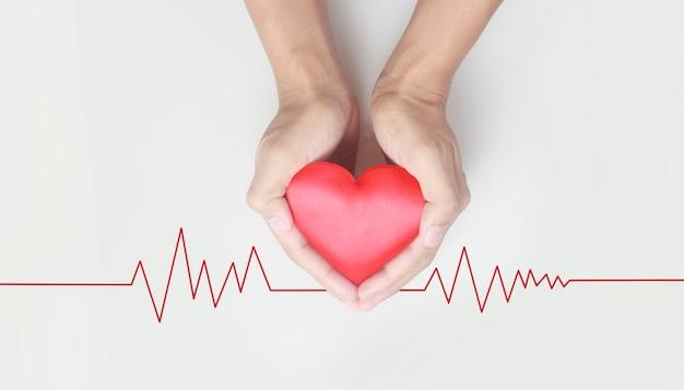 Mãos segurando um coração vermelho. conceitos de doação de saúde do coração