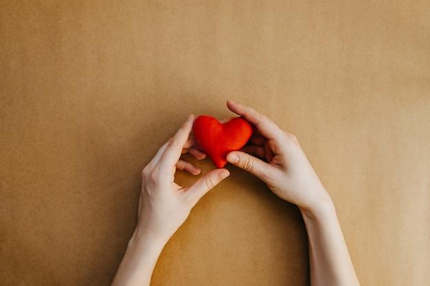 Mãos segurando um coração vermelho de brinquedo feito à mão.