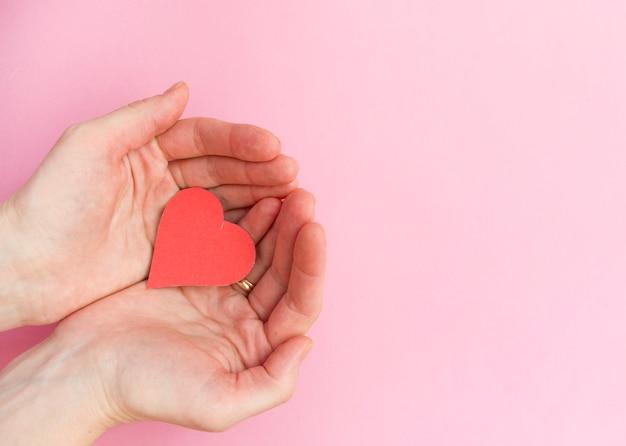 Mãos segurando um coração vermelho, saúde do coração, doação, caridade voluntária feliz, responsabilidade social de rsc, dia mundial do coração, dia mundial da saúde, dia mundial da saúde mental, lar adotivo, bem-estar, conceito de esperança