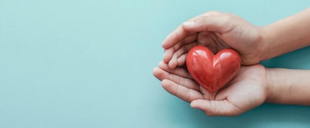 Mãos segurando um coração vermelho sobre fundo azul