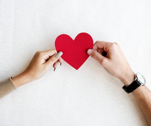 Mãos segurando um coração vermelho