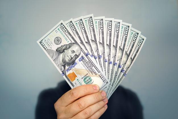 Mãos segurando um dólar em dinheiro. 1000 dólares em 100 notas em close-up da mão de um homem em um fundo escuro.