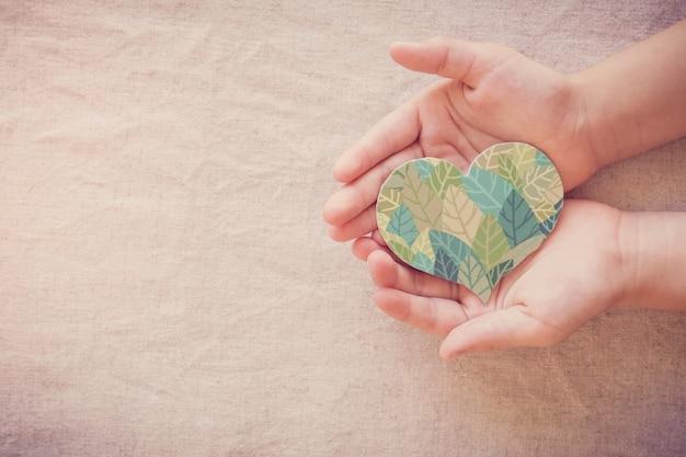 Mãos segurando um formato de coração em folha, responsabilidade social em responsabilidade social, vida ecologicamente sustentável, vegano, dia mundial do meio ambiente, dia da terra