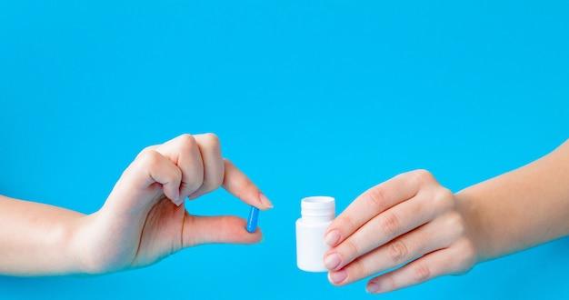 Mãos segurando um frasco branco para pílulas e comprimidos