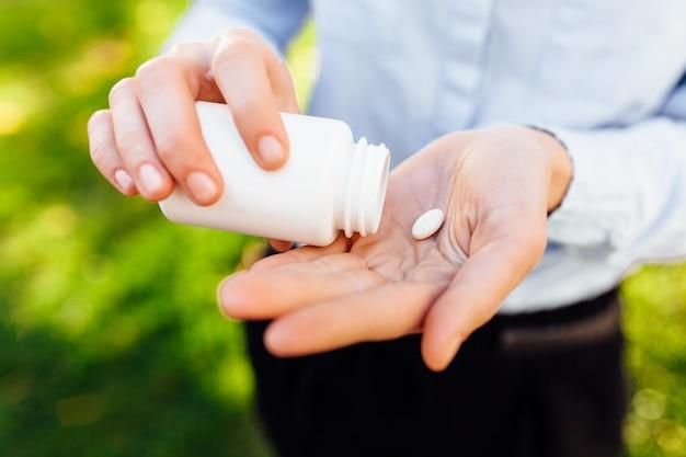 Mãos segurando um frasco com pílulas, closeup