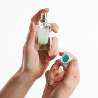 Mãos segurando um frasco de perfume