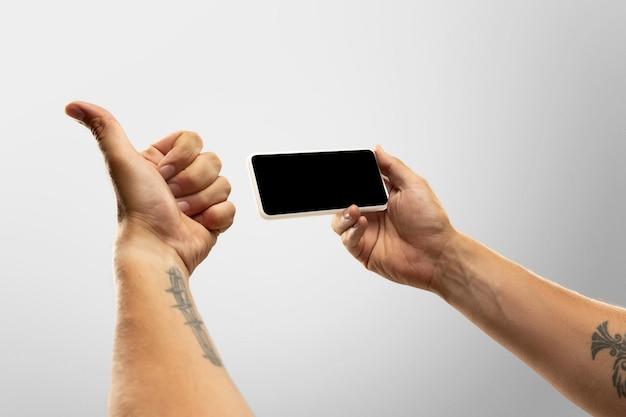 Mãos segurando um gadget em fundo branco