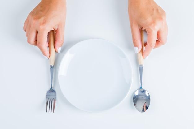 Mãos segurando um garfo e colher