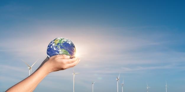 Mãos segurando um globo, terra no fundo do campo da turbina eólica. conceito de proteção ambiental mundial e energia renovável. elementos desta imagem fornecidos pela nasa