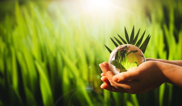 Mãos segurando um globo terrestre de cristal