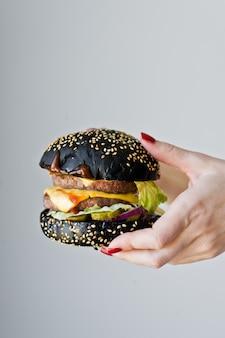 Mãos segurando um hambúrguer suculento.