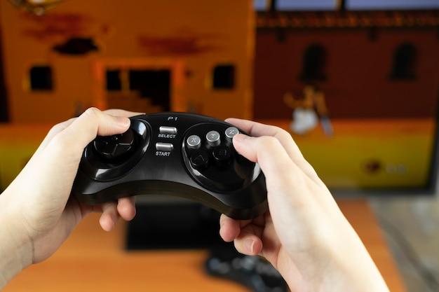 Mãos segurando um joystick retrô sem fio