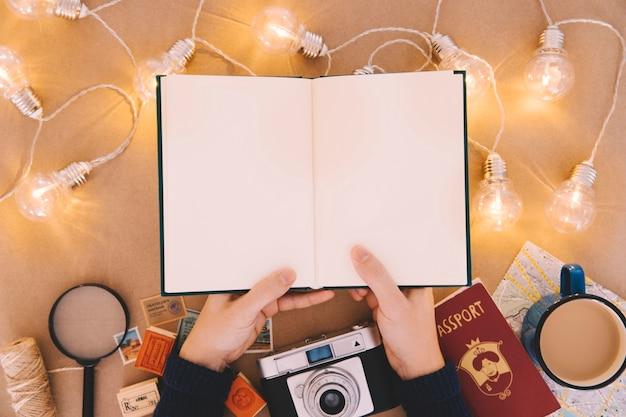 Mãos segurando um livro claro na mesa do viajante