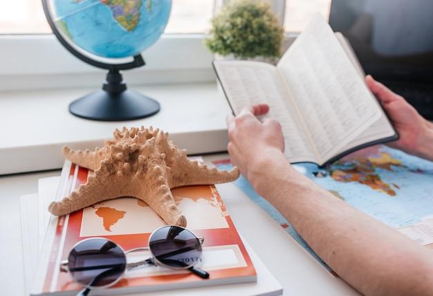 Mãos segurando um livro e estrelas do mar, um globo do mundo e um par de óculos de sol ao lado dele.
