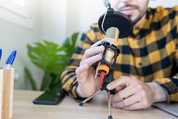 Mãos segurando um microfone enquanto grava um podcast