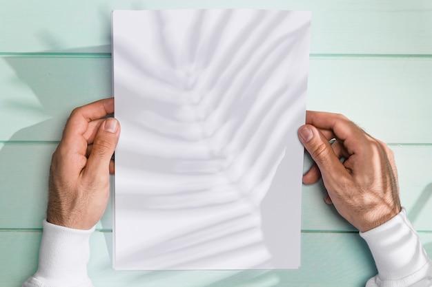 Mãos segurando um papel e sombra de folhas