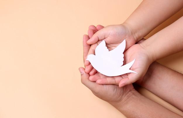 Mãos segurando um pássaro branco de papel, conceito do dia da paz mundial.