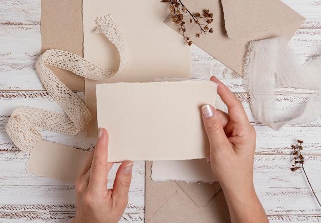 Mãos segurando um pedaço de papel de perto