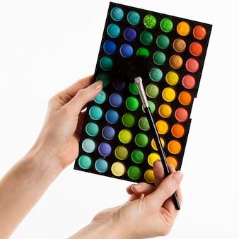Mãos segurando um pincel de maquiagem com paleta