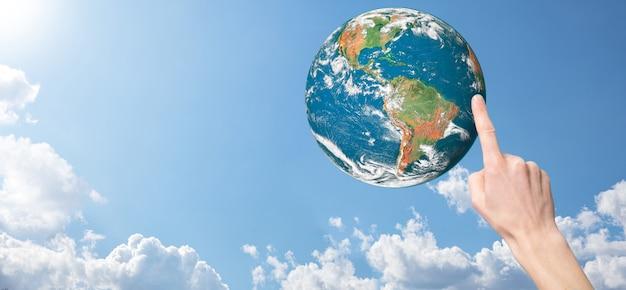 Mãos segurando um planeta, a terra em uma superfície do céu azul da natureza com lindas nuvens brancas e luz do sol