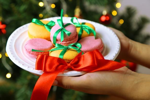 Mãos segurando um prato com biscoitos caseiros, no fundo brilhante