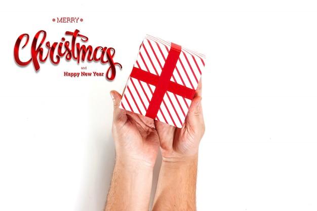 Mãos segurando um presente e uma inscrição feliz natal em um branco. cartão de natal, fundo festivo. meios mistos.