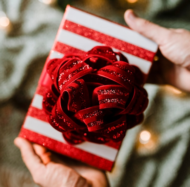 Mãos segurando um presente temático de natal