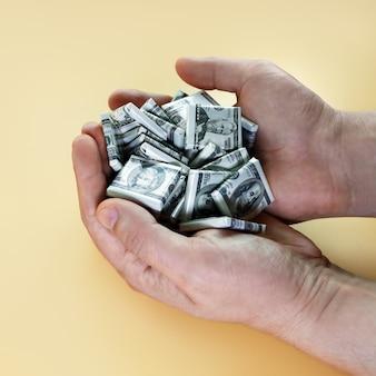 Mãos segurando um punhado de doces em forma de dólares