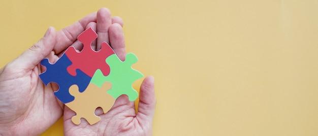 Mãos segurando um quebra-cabeça, conceito de saúde mental, dia mundial da conscientização do autismo