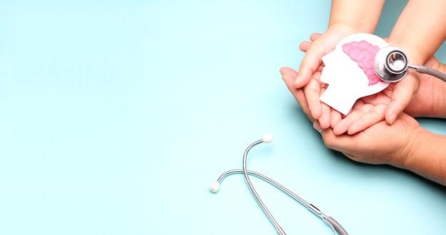 Mãos segurando um recorte de papel do cérebro de encefalografia com estetoscópio.
