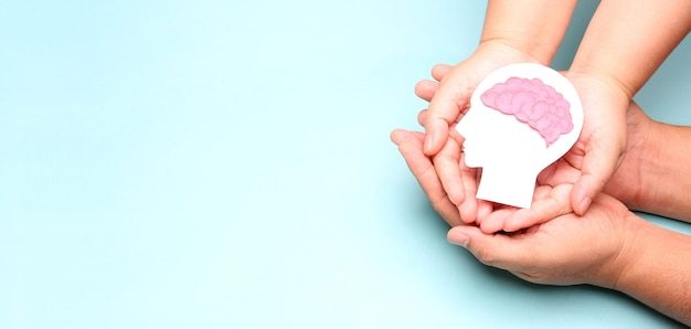 Mãos segurando um recorte de papel do cérebro de encefalografia.