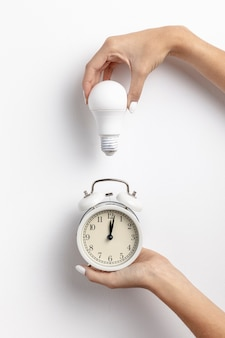 Mãos segurando um relógio e lâmpada