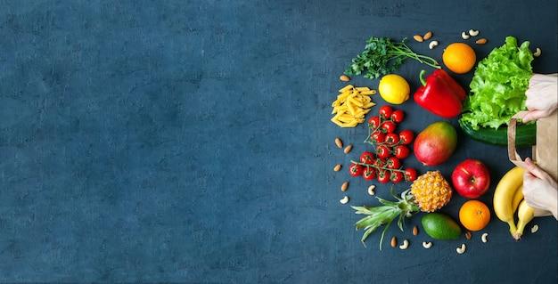 Mãos segurando um saco de papel com comida vegetariana saudável variedade de vegetais e frutas
