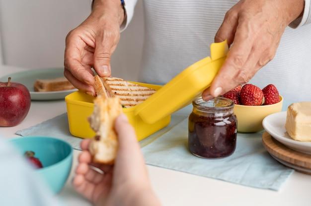 Mãos segurando um sanduíche de perto