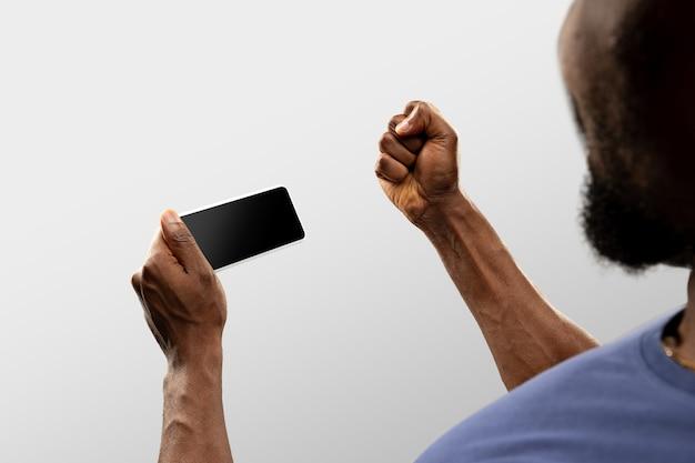 Mãos segurando um smartphone, copyspace para anúncio. fundo branco
