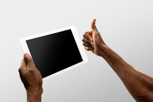 Mãos segurando um tablet, copyspace para anúncio. fundo branco